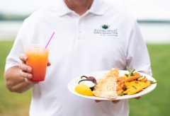 Man hold a plate with fish and vegetables and a summery drink