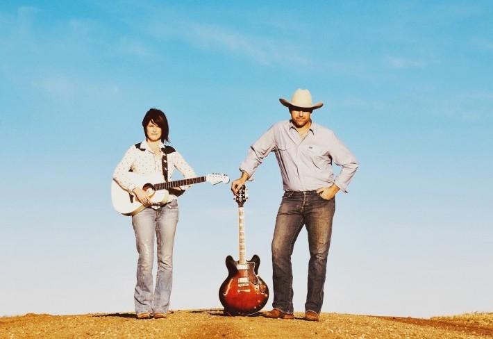 Barn Flies standing on a dirt road holding guitars